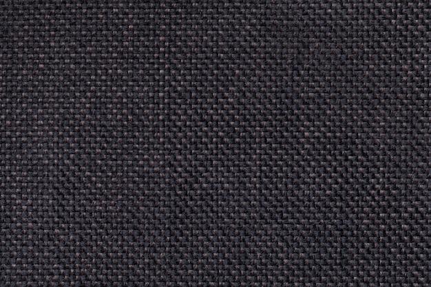 Dunkelschwarze textilhintergrundnahaufnahme. struktur des gewebemakros