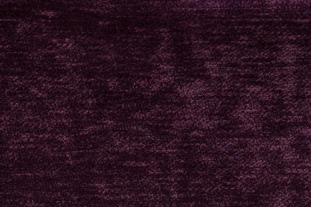 Dunkelvioletter, flauschiger hintergrund aus weichem, flauschigem stoff. textur des leichten windeltextils, nahaufnahme.