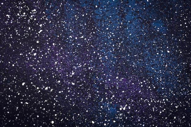 Dunkle aquarellhintergründe mit sternenhimmeleffekt. schwarze galaxie auf zeichnung, splatter-farbmuster. gefleckte kunstbeschaffenheit. abstrakte kreative magische tapete mit tintentröpfchen.