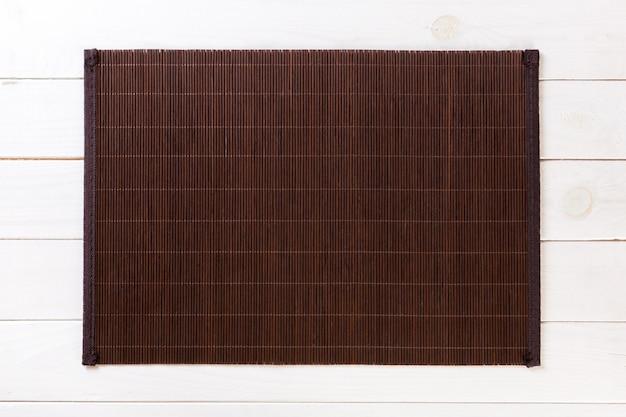 Dunkle bambusmatte auf weißem hölzernem hintergrund