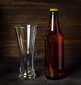 Dunkle bierflasche mit leerem glas auf dunklem holz.