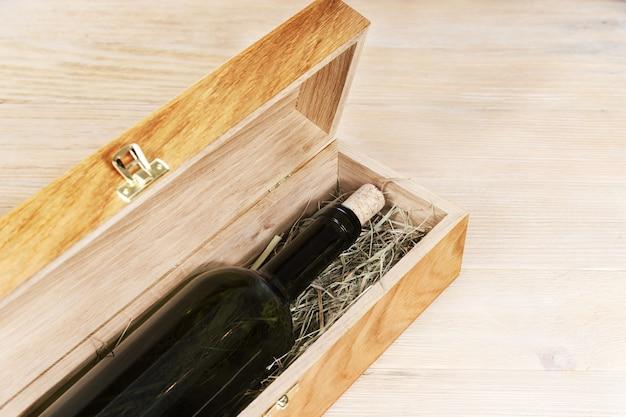 Dunkle flasche wein innerhalb des hölzernen kastens auf hölzernem hintergrund mit kopienraum. geschlossene weinflasche auf trockenem gras.