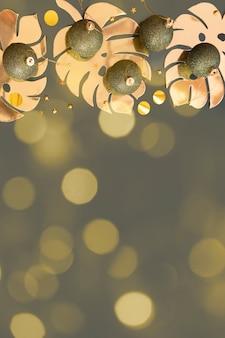 Dunkle flaschengrüne weihnachtskugeln mit goldenen monstera-blättern auf einem blaugrünen hintergrund