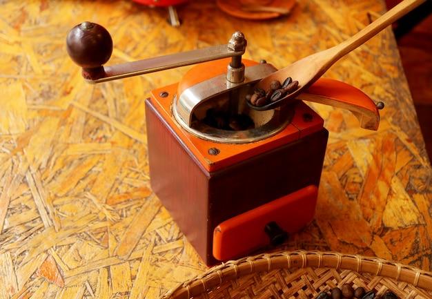 Dunkle geröstete kaffeebohnen in eine kaffeemühle für hausgemachten kaffee geben