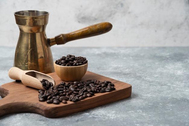 Dunkle geröstete kaffeebohnen und kaffeemaschine auf holzschneidebrett.