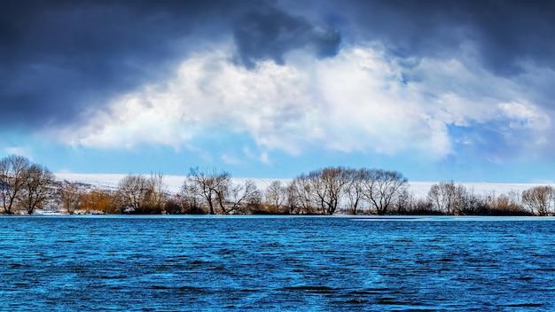Dunkle gewitterwolken im winter über dem fluss