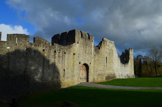 Dunkle gewitterwolken über den ruinen von desmond castle in irland.