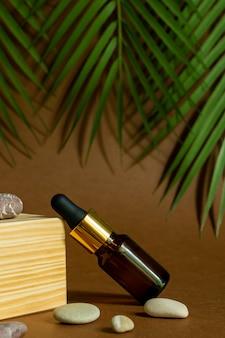 Dunkle glasflasche mit pipette oder tröpfchen. mock up essential liquid. trendiger hintergrund mit holzsockel, tropischen blättern und seesteinen.