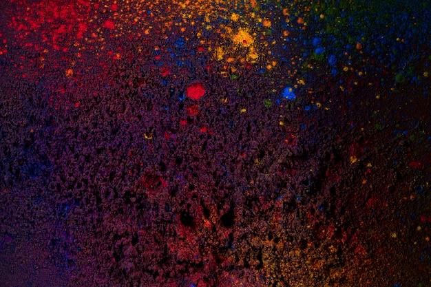 Dunkle holi-farben bespritzt auf schwarzem hintergrund