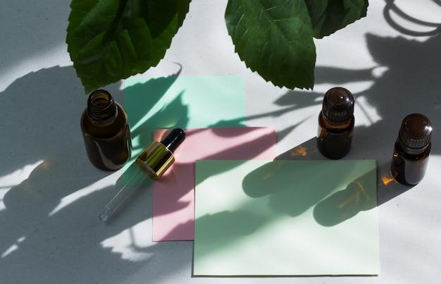 Dunkle kosmetische flaschen und grüne natürliche blätter auf einem hellen hintergrund. grüne leere karte, blatt zum schreiben. layout zum hinzufügen von inschriften. natürliches hartes licht, tiefe schatten.