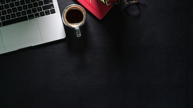 Dunkle ledertabelle des büros mit laptop, rotem anmerkungsbuch, kaffee und kopienraum