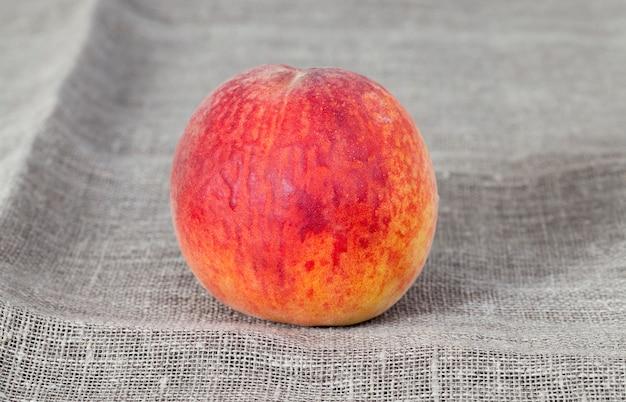 Dunkle leinentischdecke mit einem reifen süßen pfirsich, nahaufnahme