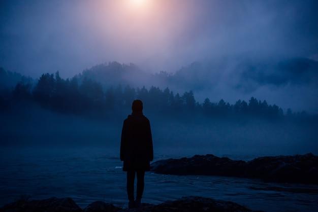 Dunkle menschliche silhouette in einem dichten nebel vor dem hintergrund von wald, hügeln und bergfluss. geheimnisvolle weibliche figur am wüstenufer. apokalyptische landschaft, luftverschmutzung.
