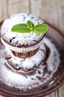 Dunkle muffins der frischen schokolade mit zuckerpulver und minze treiben auf brauner platte auf rustikalem holztisch blätter