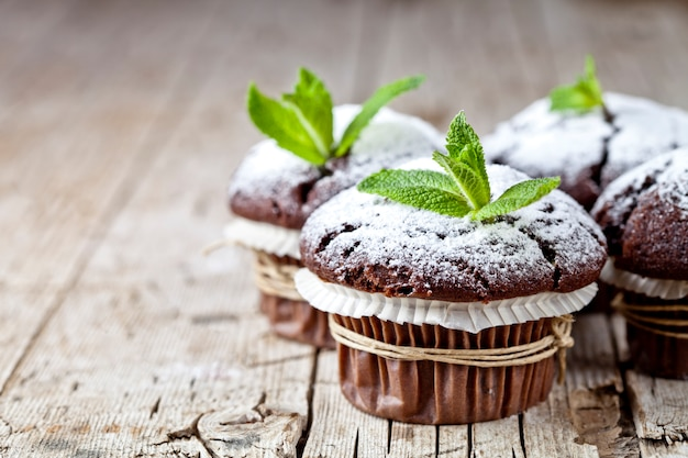 Dunkle muffins der frischen schokolade mit zuckerpulver und minze treiben auf rustikalem holztischhintergrund blätter.