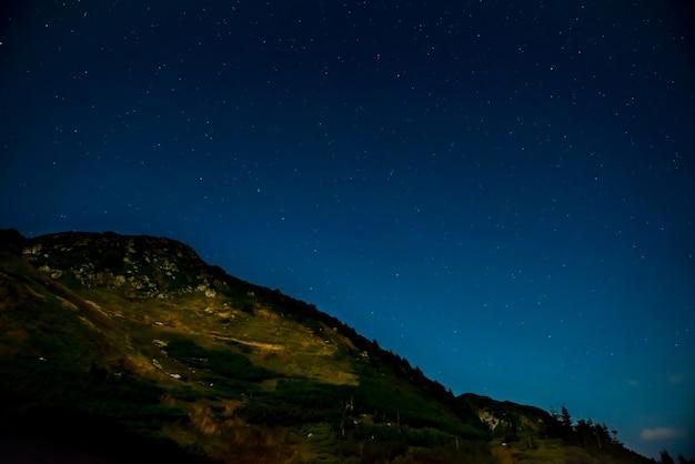 Dunkle nacht mit sternen am himmel über dem berg