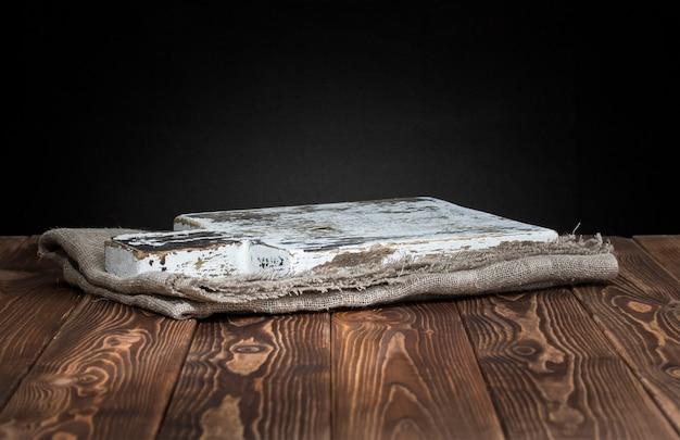 Dunkle oberfläche mit altem schneidebrett auf einem sackleinen
