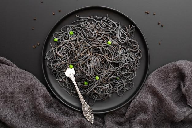 Dunkle pastateller auf einem dunklen tuch