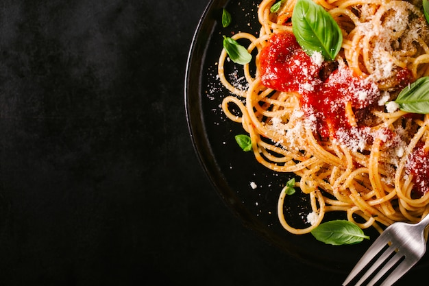 Dunkle platte mit italienischen spaghetti auf dunkelheit