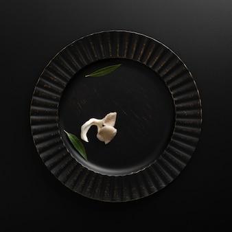 Dunkle platte mit pilz auf einer dunklen tabelle