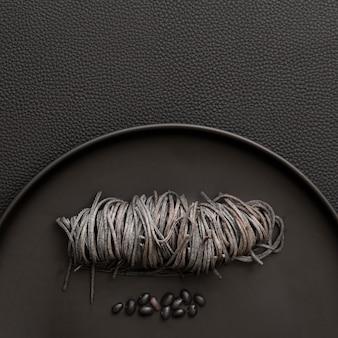 Dunkle platte mit teigwaren und bohnen auf einer dunklen tabelle