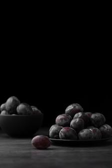 Dunkle platte und schüssel mit pflaumen auf einem dunklen hintergrund