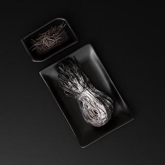 Dunkle platten mit schwarzen teigwaren auf einem dunklen hintergrund