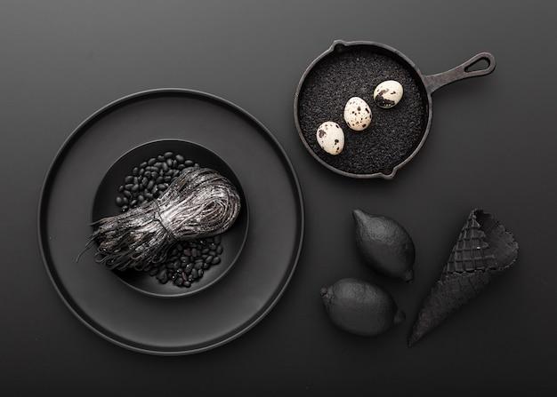 Dunkle platten mit teigwaren und eiern mit bohnen auf einem dunklen hintergrund