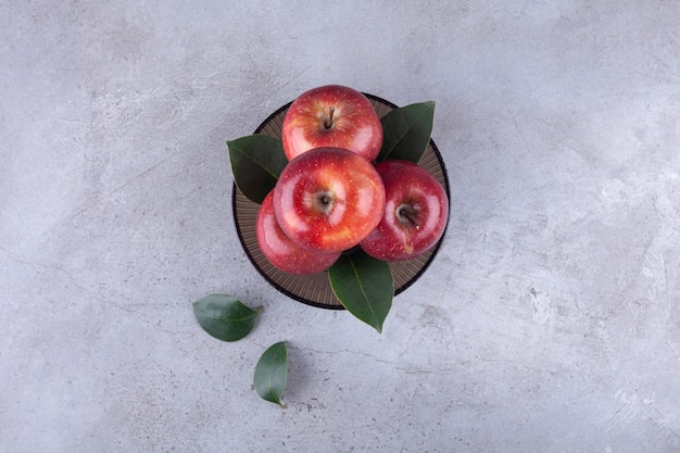Dunkle schale mit leuchtend roten äpfeln auf stein.