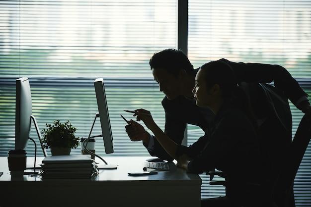 Dunkle schattenbilder von den kollegen, die auf bildschirm im büro gegen fenster zeigen