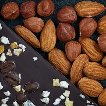 Dunkle schokolade mit kaffeebohnen, früchten und mit mandeln auf dunklem steinhintergrund