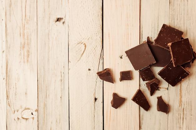 Dunkle schokolade ohne zucker und glutenfrei für diabetiker und allergiker. in stücke zerbrochene schwarze schokolade liegt auf einem weißen tisch im rustikalen stil.