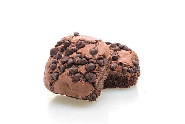 Dunkle schokoladen-brownies gekrönt von schokoladenstückchen, die auf weißem tisch isoliert werden