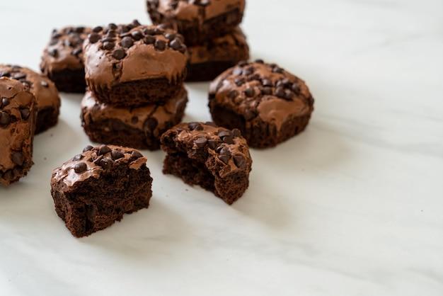Dunkle schokoladenbrownies mit schokostückchen oben drauf