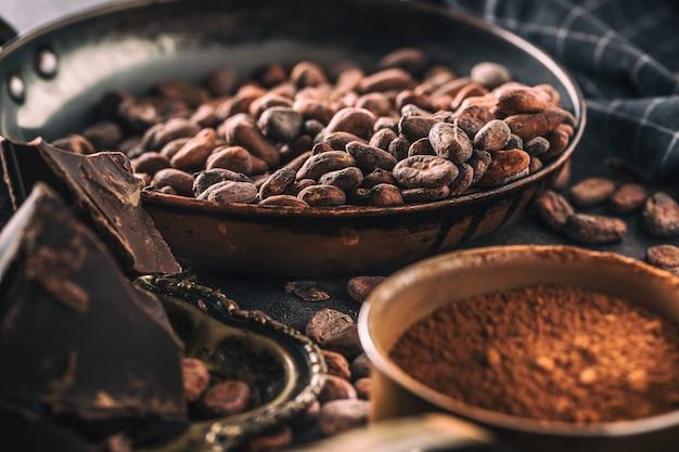 Dunkle schokoladenkakaobohnen und -pulver auf betontisch.