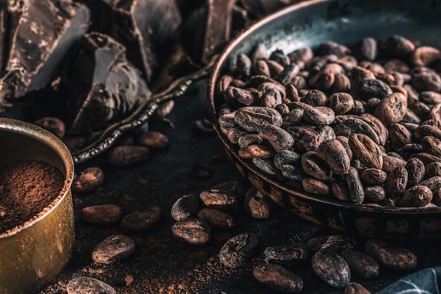 Dunkle schokoladenkakaobohnen und -pulver auf betontisch. Premium Fotos
