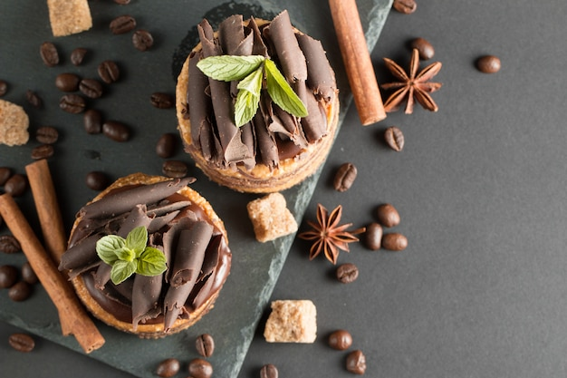 Dunkle schokoladenkuchen auf schwarzem slattern brett mit minze, zimt, kaffeebohnen auf einem hölzernen hintergrund. tasty dessert food-konzept.