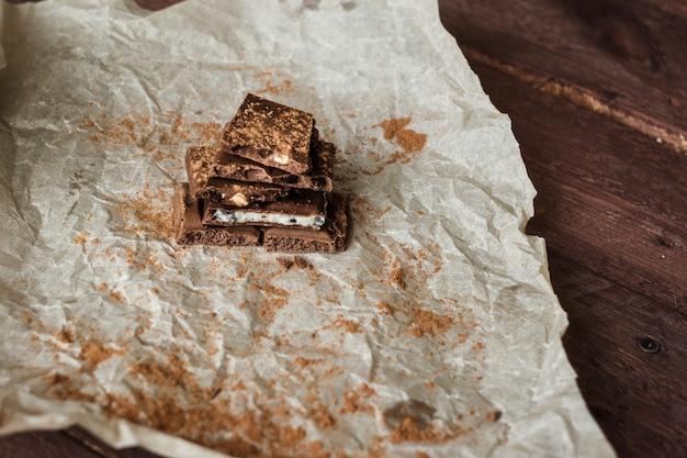 Dunkle schokoladenrinde mit gemischten füllungen auf wachspapier