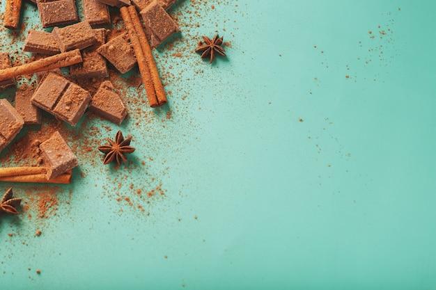 Dunkle schokoladenscheiben mit zimt und gewürzen auf pastellgrüner oberfläche