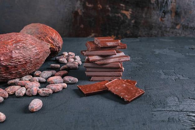 Dunkle schokoladenstücke und kakaobohnen auf tabelle