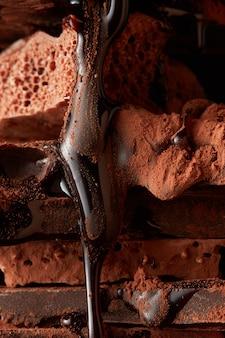 Dunkle schokoladenstücke und schokoladensirup nahaufnahme