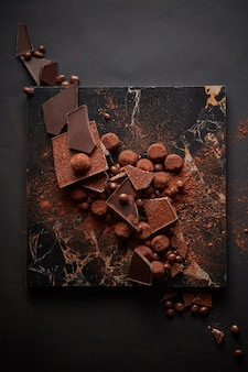 Dunkle schokoladentrüffel in verschüttetem kakaopulver auf dunklem marmorteller