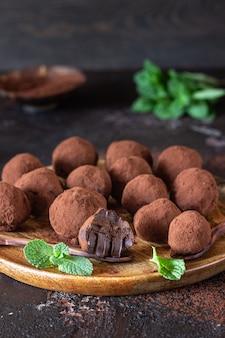Dunkle schokoladentrüffelsüßigkeit mit rohem kakaopulver und minze