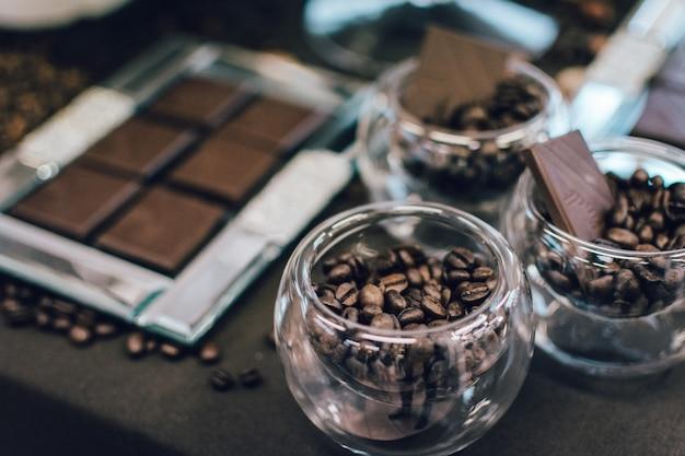 Dunkle schokoriegel und kaffeebohnen in den schüsseln