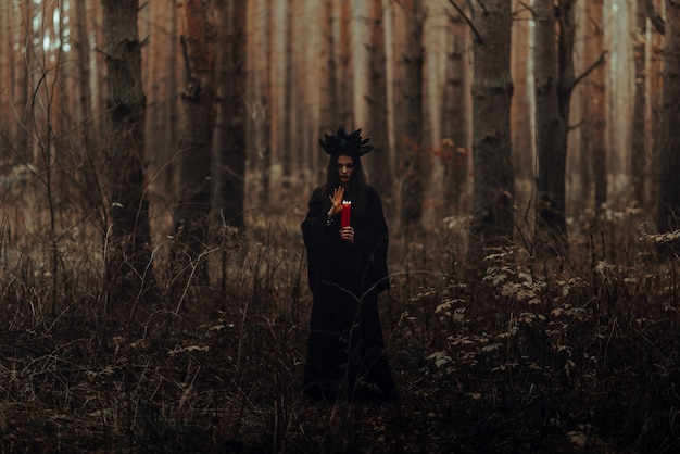 Dunkle schreckliche hexe mit kerzen in den händen führt ein okkultes mystisches ritual im wald durch