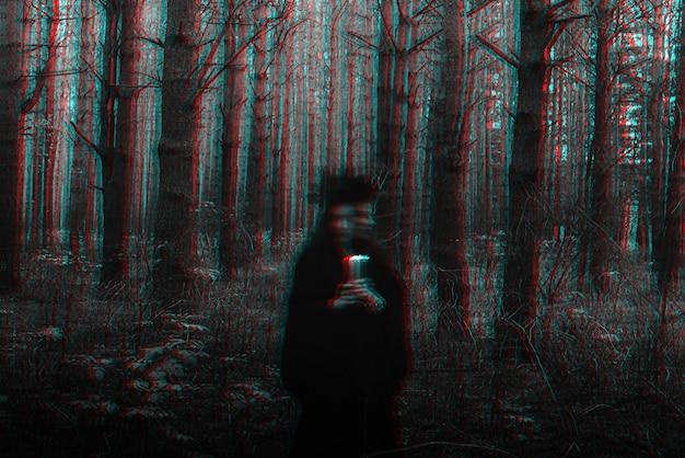 Dunkle schreckliche hexe mit kerzen in ihren händen führt ein okkultes mystisches ritual durch. unscharfes foto mit unschärfe aufgrund langer belichtungszeit. schwarzweiß mit 3d-glitch-virtual-reality-effekt