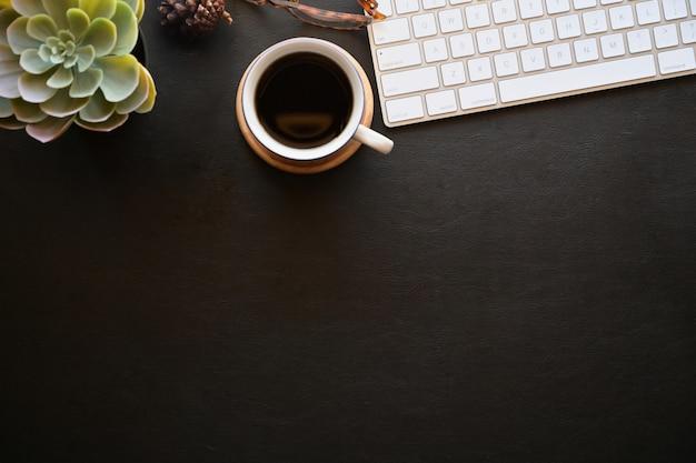Dunkle schreibtischtischplatte des büro-leders mit tastaturcomputer, büroartikel, gläser