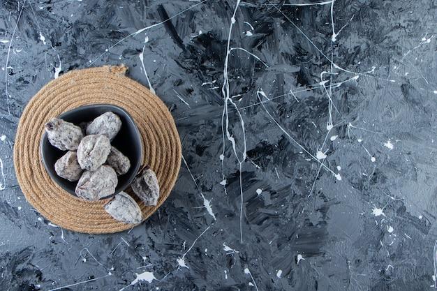 Dunkle schüssel mit getrockneten leckeren kakis auf marmorhintergrund.