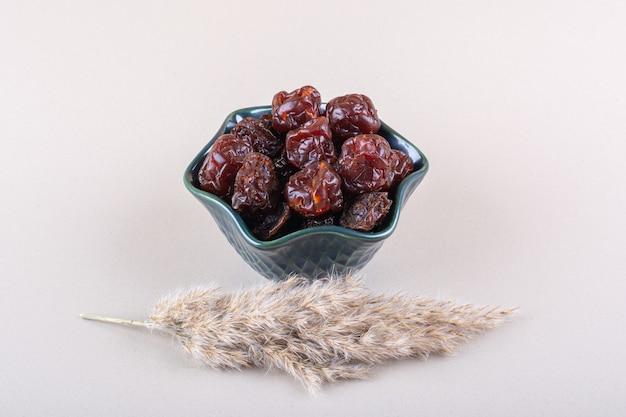 Dunkle schüssel organische trockene datteln auf weißem tisch. foto in hoher qualität