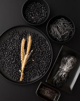 Dunkle schüsseln mit teigwaren und bohnen auf einem schwarzen hintergrund